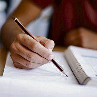 foto de uma pessoa escrevendo, onde aparece um livro, um caderno e um lápis.
